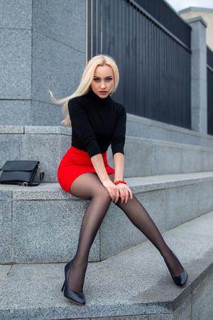 Hermosa chica rubia en falda roja con piernas perfectas en pantimedias y zapatos con tacones posando al aire libre en la plaza de la ciudad. Foto de archivo