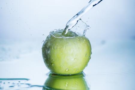 Grüner Apfel mit gefrorenem Wasserspritzer und -tropfen ohne Bildbearbeitung und Retusche. Standard-Bild