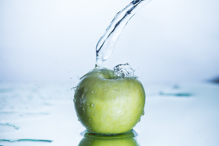Green apple with freezed water splash and drops without image editing and retouch. Stock Photo