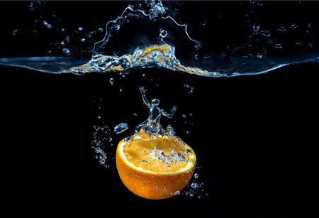 Orange with frozen water splash and drops on the black background - with man figure that formed from the water bubbles. Conceptual photo - thirst.