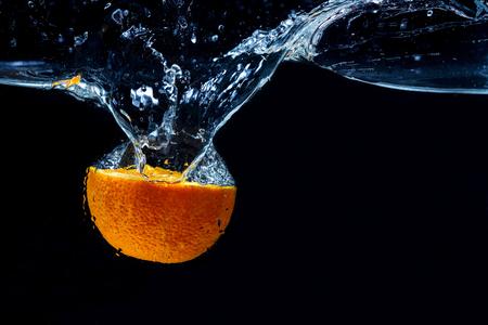 Arancione con spruzzi d'acqua congelata e gocce sullo sfondo nero - succhi di frutta appena spremuti estivi sani.