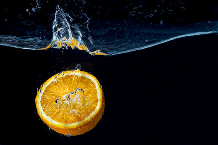 Orange with frozen water splash and drops on the black background - healthy summer freshly squeezed fruit juices.