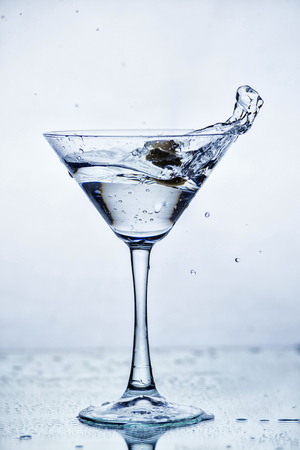 Martini glass with frozen splashing drops of drink - motion frozen close-up picture isolated on the white background. Stock Photo