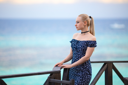 Pretty blonde girl in the dark dress on the lonely romantic evening beach in the rays of the setting sun.