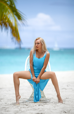 Beautiful blonde girl in blue dress sitting on the white chair on the lonely tropical beach with turquoise water and white sand. Saona, Dominican Republic.