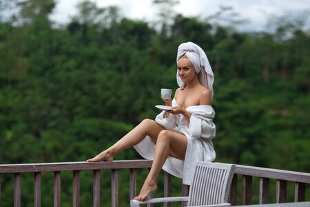 Beautiful sexy blonde woman with perfect legs in the white bathrobe and towel sitting on the old tropical balcony with a cup of coffee in the rays of the morning sun. Фото со стока