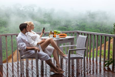 Young couple man and woman - breakfast on the rainy jungle balcony with morning coffee and fruits.