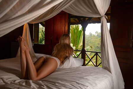 Beautiful sexy blonde woman posing on the bed of the traditional wooden house in the tropical forest with a jungle valley view. Bali. Ubud. Stock Photo