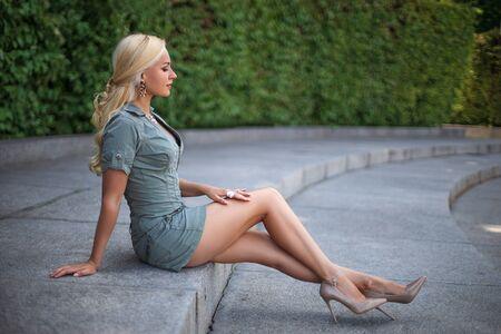 Schönes blondes Mädchen im grünen Kleid mit perfekten Beinen und Schuhen mit High Heels posiert im Freien auf dem Stadtplatz.
