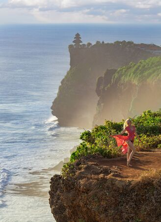 Woman in the red dress posing on the lonely cliff above the ocean in the rays of setting sun. Bali, Uluwaty.