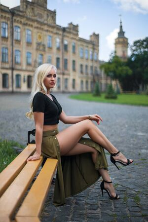 Beautiful blonde girl in the green dress with perfect legs and shoes with high heels posing outdoor on the city square. Фото со стока - 128506837