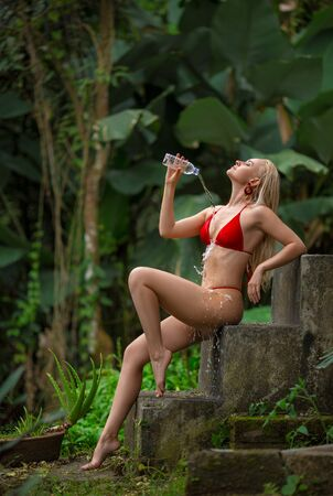 Beautiful blonde girl in the red swimsuit posing with a bottle of water on the old stone stairs in the jungle forest. Hot weather. Bali, Ubud.