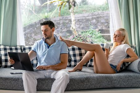 Young couple man and woman freelancer at work with laptop and the girl with perfect legs and with morning coffee.