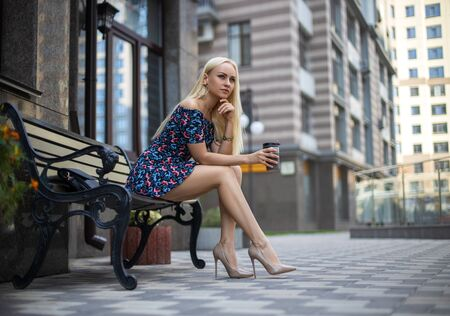 Beautiful blonde girl with perfect legs posing outdoor on the city street with coffee thermos mug.