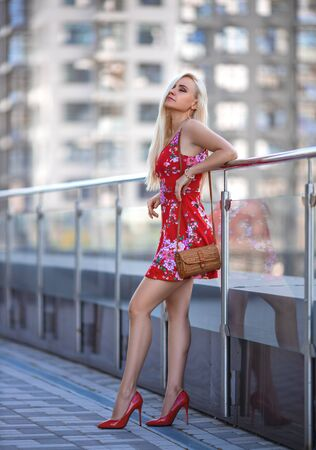 Beautiful blonde woman in the red dress and high heels posing outdoor on the city square. Фото со стока