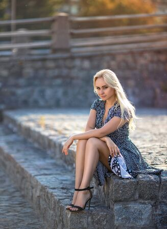 Beautiful blonde girl in the dotted dress with perfect legs and shoes with high heels posing outdoor on the city square in the light of setting sun. Фото со стока - 129606604