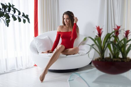 Beautiful sexy brunette woman in the red body posing on the sofa in the white bedroom.
