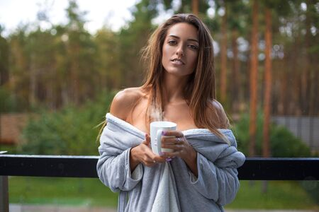 Beautiful woman in the bathrobe with morning coffee cup on the balcony with forest background and the rain - beauty portrait.
