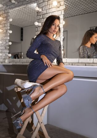 Beautiful brunette woman in sexy short dress and high heels posing on the chair in the makeup studio near mirror - beauty close-up portrait