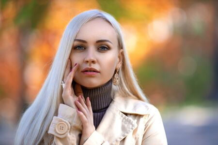 Beautiful girl posing on the street in the autumn park in the light of setting sun. Beauty close up portrait.