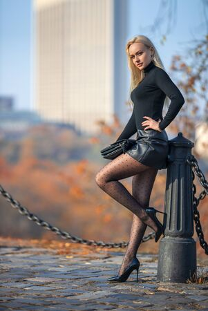 Beautiful blonde woman posing outdoor in the autumn park in the lights of setting sun.