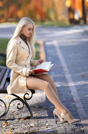 Chica estudiante hermosa con piernas perfectas sentado en el banco y leyendo el libro en el parque de otoño en las luces del sol poniente. Foto de archivo