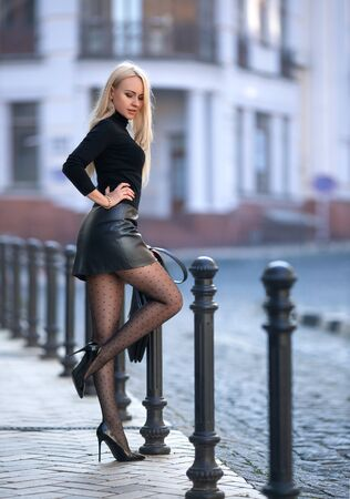 Beautiful blonde woman posing outdoor in the autumn street in the lights of setting sun. Фото со стока - 133945717