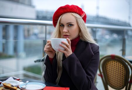 Beautiful woman posing in the street cafe in a red cap with tea cup in the evening. France. Beauty close-up portrait. Фото со стока - 133880418