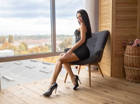 Beautiful brunette girl with perfect legs sitting on the chair near the window in the lights of setting sun. Фото со стока