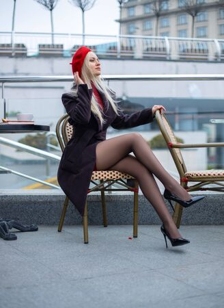 Beautiful woman with perfect legs in tights posing in the street cafe in a red cap with tea cup in the evening.