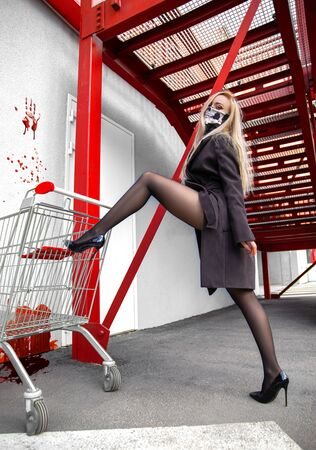 Beautiful blonde bandit girl with perfect legs in pantyhose posing outdoor posing near shopping cart and blood - photo about rebel, crisis and mass panic.