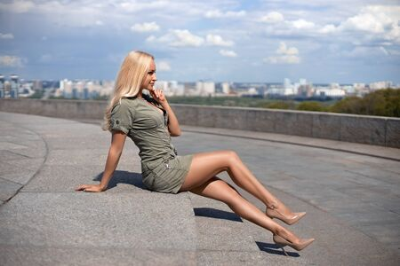 Beautiful blonde girl in the green dress with perfect legs and shoes with high heels posing outdoor on the city square. Stock Photo