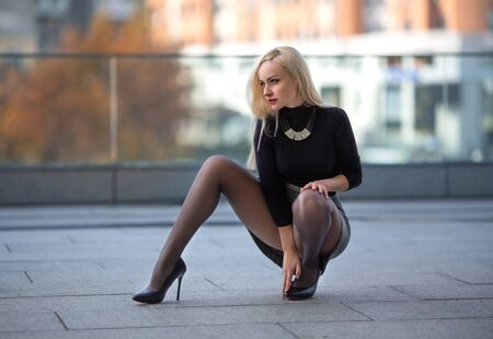 Beautiful blonde girl with perfect legs in pantyhose and shoes with high heels posing outdoor on the city square.