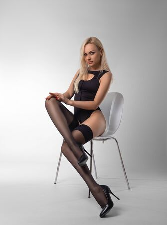 Sexy blonde woman with perfect legs posing in black stockings and lingerie at the white chair on the gray background.
