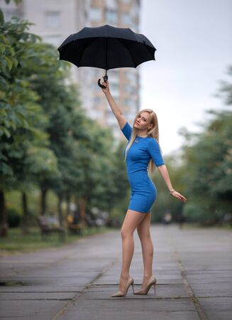 Beautiful blonde girl in a blue dress with perfect legs in pantyhose and shoes with high heels posing with umbrella under the rain.