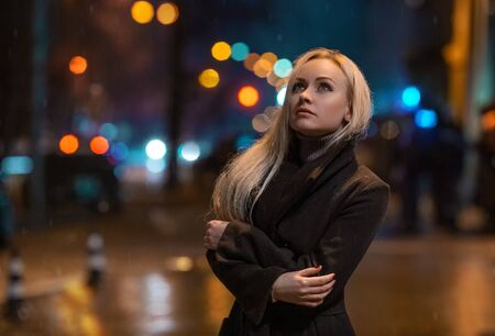 Beautiful girl walks in the rainy street in the lights of the night city. Beauty portrait with bokeh.
