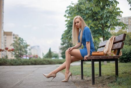 Beautiful blonde girl in a blue dress with perfect legs in pantyhose and shoes with high heels sitting on the bench in the park.