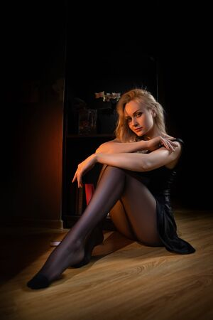 Beautiful blonde woman with perfect legs posing in black pantyhose on the dark background at home. 免版税图像