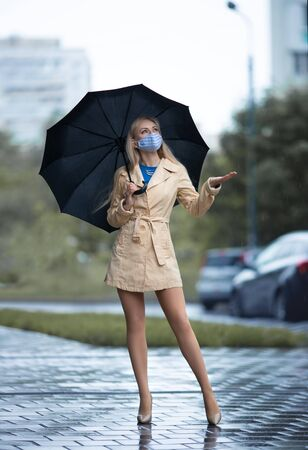 Beautiful blonde girl in a face mask with perfect legs in pantyhose and shoes with high heels posing with umbrella under the rain.