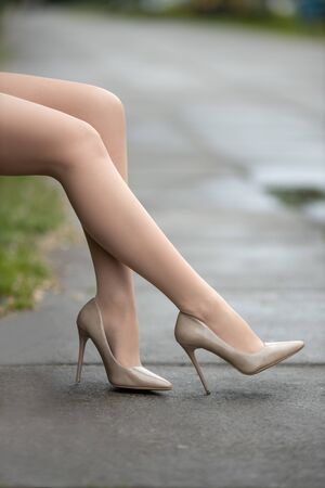 Beautiful woman with perfect legs in pantyhose and shoes with high heels posing outdoor on the city square. 免版税图像
