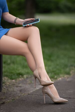 Beautiful woman with perfect legs in pantyhose and shoes with high heels and with the mobile phone sitting on the bench in the city square.