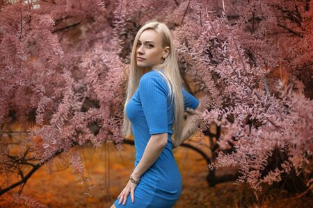 Closeup portrait of the beautiful blonde woman near blooming pink acacia tree - close up beauty portrait.