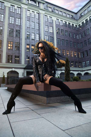 Beautiful brunette girl in high boots on heels and with perfect butt posing outdoor on the city square.