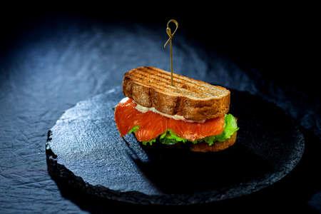 Sandwich with fresh salmon and salad on black platter on black background - close-up food photo 免版税图像