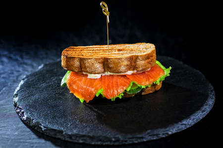 Sandwich with fresh salmon and salad on black platter on black background - close-up food photo