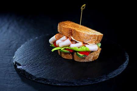 Sandwich with hamon and salad on black platter on black background - close-up food photo