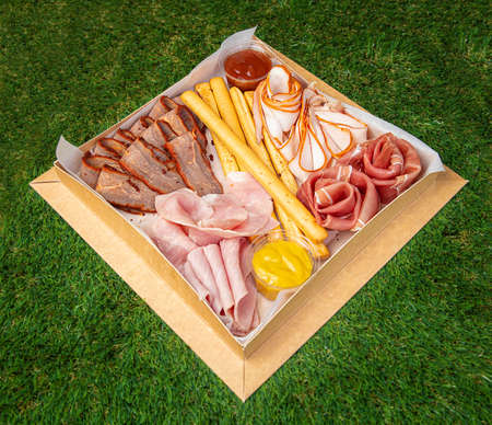 Picnic basket with different snacks, cheese and meat on the green grass - close-up food photo
