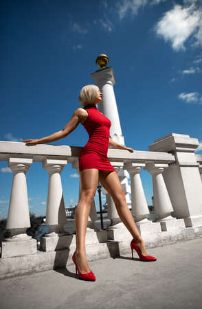 Beautiful blonde girl in the red dress with perfect legs and shoes with high heels posing outdoor on the city square.