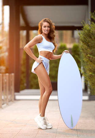 Beautiful fitness girl with a perfect body posing outdoor with wakeboard in the rays of sun-set. Stock Photo