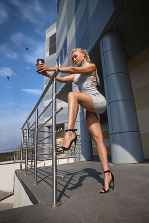 Beautiful blonde girl in grey dress with perfect legs and shoes with high heels posing outdoor at the city square. Street fashion photo with the swift birds in the sky.